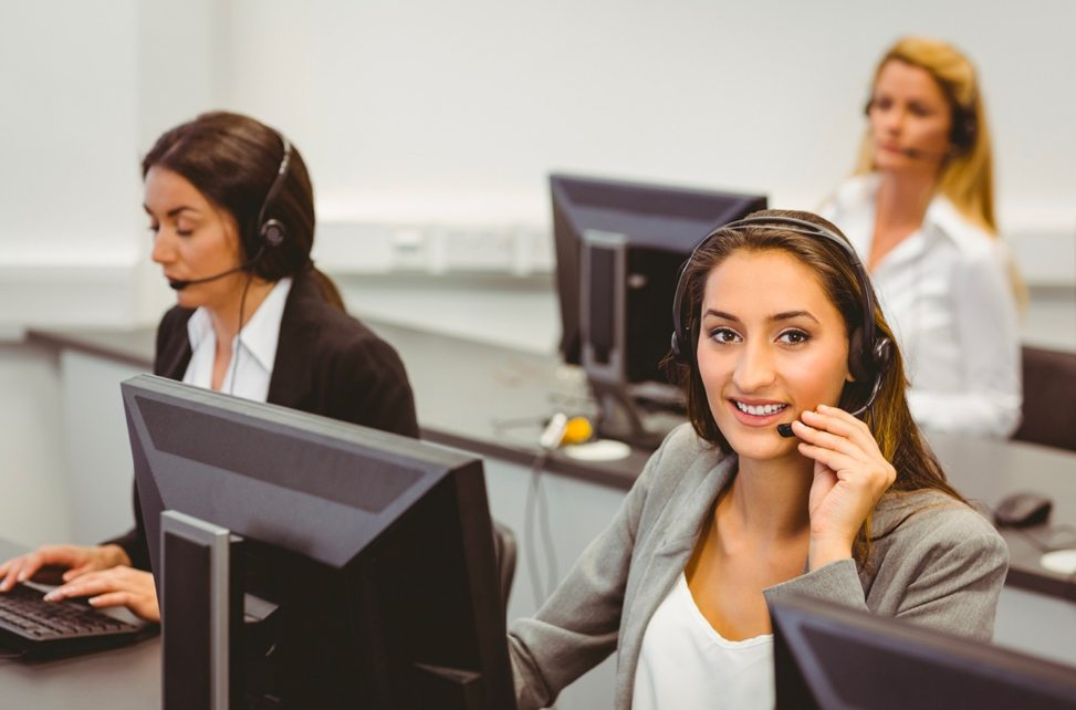 3 women in a call center answering the phone using headsets.