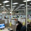 Call Center with numerous people answering telephone calls for businesses.