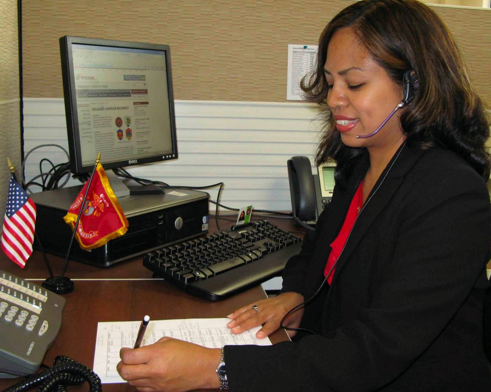 a call center rep with a headset writing down notes pertaining to a phone call