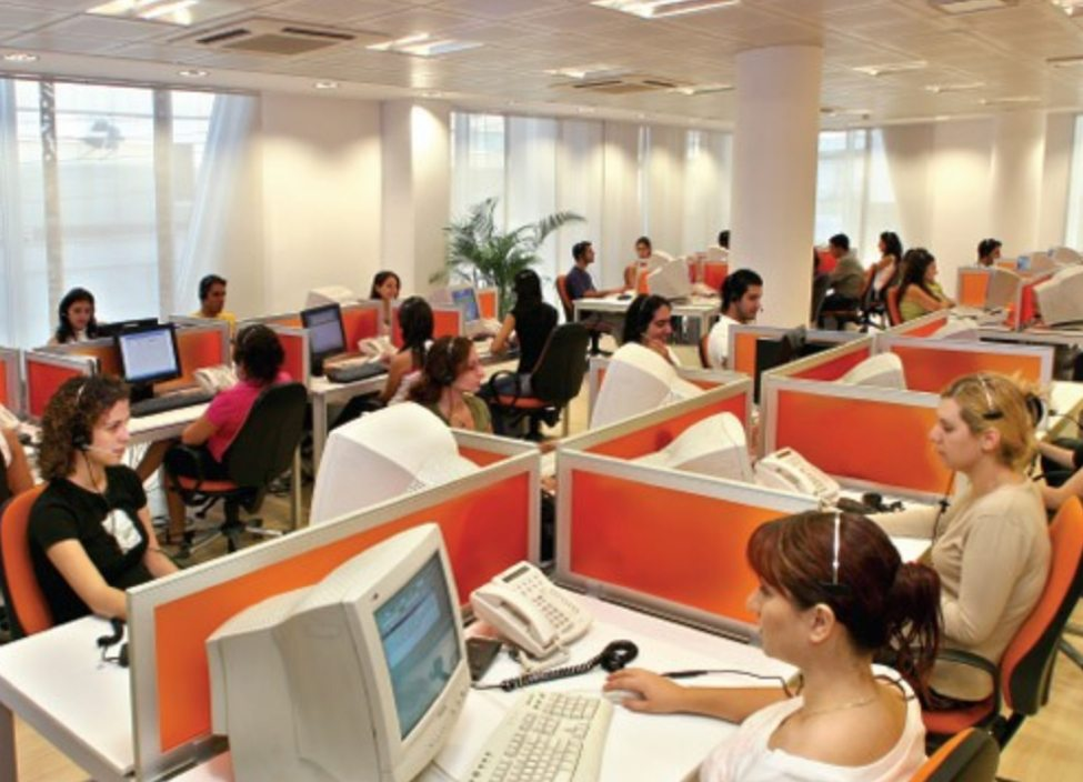 call center with numerous of employees wearing headsets answering the telephone